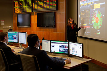 photo of a student doing a presentation in the trading room