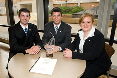 photo of three business students with an award